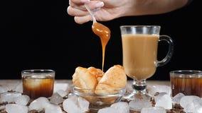 Caffè con i croissant deliziosi sulla lastra di vetro Caramello liquido puro caldo che piove a dirotto sul dessert al rallentator stock footage