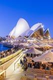 Caffè con la gente e Sydney Opera House a penombra Immagine Stock