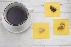 Caffè con la tazza bianca ed i dadi misti sulla tavola bianca Immagine Stock Libera da Diritti