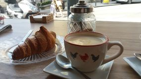 Caffè con latte ed il croissant dolce vicino all'ufficio immagini stock libere da diritti
