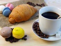 Caffè, croissant e macarones giranti sulla tavola di legno Immagine Stock Libera da Diritti