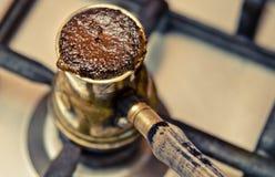 Caffè d'ebollizione nel cezve sulla stufa Fotografia Stock