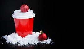 Caffè da andare nelle decorazioni rosse di natale e della tazza sul nero immagine stock