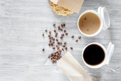 Caffè da andare Tazze di caffè con i chicchi di caffè e della copertura sulla vista superiore del backound di legno della tavola immagini stock