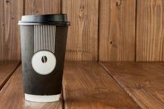 Caffè da portar via in termo tazza su un fondo di legno, spazio della copia immagine stock