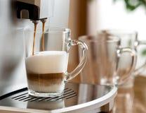 Caffè del cappuccino che prepara in tazza di vetro con la macchina immagini stock
