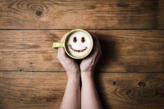 Caffè del cappuccino con il fronte sorridente sulla tavola di legno Immagini Stock Libere da Diritti