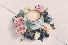 Caffè del cappuccino e composizione nei fiori su legno bianco Fotografie Stock Libere da Diritti