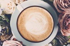 Caffè del cappuccino e composizione nei fiori su legno bianco Immagine Stock Libera da Diritti