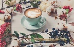 Caffè del cappuccino e composizione nei fiori su legno bianco Immagini Stock