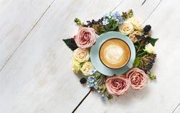 Caffè del cappuccino e composizione nei fiori su legno bianco Fotografia Stock Libera da Diritti