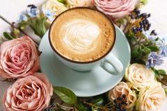 Caffè del cappuccino e composizione nei fiori su legno bianco Fotografie Stock