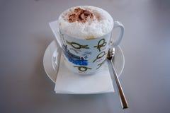 Caffè del cappuccino in tazza della porcellana con le istruzioni del recipiente del nodo Fotografie Stock
