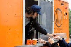 Caffè del servizio dell'uomo dal camion dell'alimento Fotografie Stock Libere da Diritti