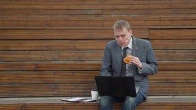 Caffè dell'uomo d'affari ed hamburger beventi di cibo stock footage