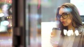Caffè della bella giovane donna o tè ed utilizzare beventi il computer della compressa nel caffè Rallentatore video d archivio