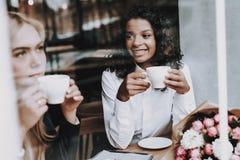 Caffè della bevanda Ragazza bionda mulatto siedasi Caffè immagini stock