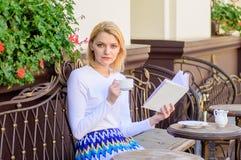 Caffè della bevanda della ragazza mentre libro colto del bestseller dall'autore popolare La donna ha terrazzo del caffè della bev fotografia stock