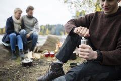 Caffè della macinazione dell'uomo con gli amici al campeggio fotografia stock libera da diritti