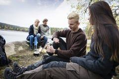 Caffè della macinazione delle coppie con gli amici durante il campeggio immagini stock libere da diritti