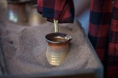 Caffè della sabbia di fabbricazione in un cezve di rame Caffè turco, caffè georgiano fotografia stock