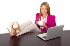 Caffè della tenuta della donna nell'ufficio con il computer portatile immagini stock libere da diritti