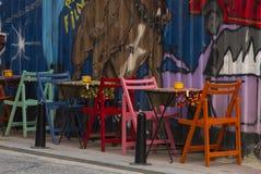 Caffè della via con le tavole di colori e le sedie e lo spirito differenti della parete fotografie stock libere da diritti