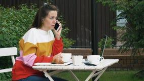 Caffè delle bevande della donna e parlare sul telefono cellulare archivi video