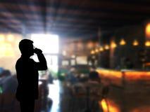 Caffè dello zip dell'uomo della siluetta con il fondo della caffetteria della sfuocatura Fotografia Stock