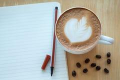 Caffè di arte del Latte e chicchi di caffè arrostiti con papernote al mattino Fotografie Stock Libere da Diritti
