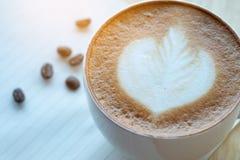 Caffè di arte del Latte e chicchi di caffè arrostiti con papernote al mattino Fotografia Stock