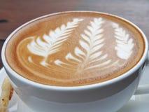 Caffè di arte del Latte sullo scrittorio di legno Fotografia Stock