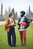 Caffè di conversazione e bevente delle coppie dei pantaloni a vita bassa per andare Immagine Stock