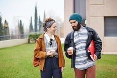 Caffè di conversazione e bevente delle coppie dei pantaloni a vita bassa per andare Fotografie Stock Libere da Diritti