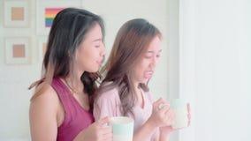 Caffè di conversazione e bevente delle coppie felici lesbiche delle giovani donne asiatiche in camera da letto a casa video d archivio