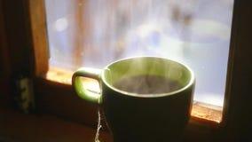Caffè di cottura a vapore caldo delizioso che sta vicino alla finestra, movimento lento di mattina video d archivio