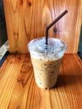 Caffè di ghiaccio in tazza di plastica e tubo marrone sulla tavola di legno fotografia stock libera da diritti