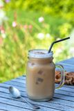 Caffè di ghiaccio in tazza di vetro con latte e cannella sulla tavola di legno nel giardino immagine stock libera da diritti