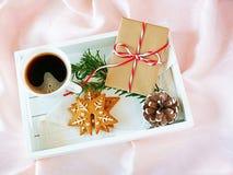 Caffè di mattina di natale con i biscotti ed il regalo del pan di zenzero sul vassoio bianco sopra seta rosa immagini stock libere da diritti