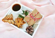 Caffè di mattina di natale con i biscotti ed il regalo del pan di zenzero sul vassoio bianco sopra seta rosa immagine stock libera da diritti