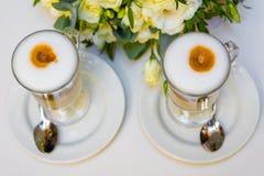 Caffè di mattina per le coppie nell'amore Due tazze di cappuccino con arte del latte sulla tavola nera Immagine Stock