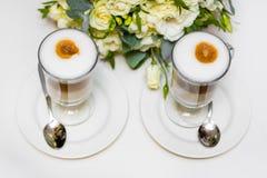 Caffè di mattina per le coppie nell'amore Due tazze di cappuccino con arte del latte sulla tavola nera Fotografie Stock Libere da Diritti