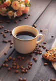 Caffè di mattina in una tazza bianca su una tavola marrone con i fiori e la cannella Fotografia Stock