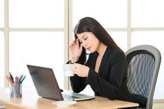 Caffè di pensiero e bevente della giovane donna di affari asiatica in di Fotografia Stock