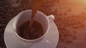Caffè di versamento circondato dai chicchi di caffè archivi video