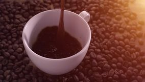 Caffè di versamento circondato dai chicchi di caffè stock footage