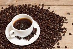 Caffè di versamento con i chicchi di caffè rosted in tazza bianca Fotografia Stock