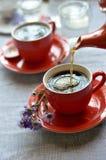 Caffè di versamento da una teiera rossa in una tazza rossa Immagini Stock