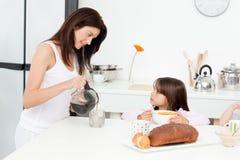 Caffè di versamento della mamma graziosa durante la prima colazione Fotografia Stock