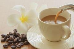 Caffè di versamento dentro alla tazza ed ai grani Fotografie Stock Libere da Diritti